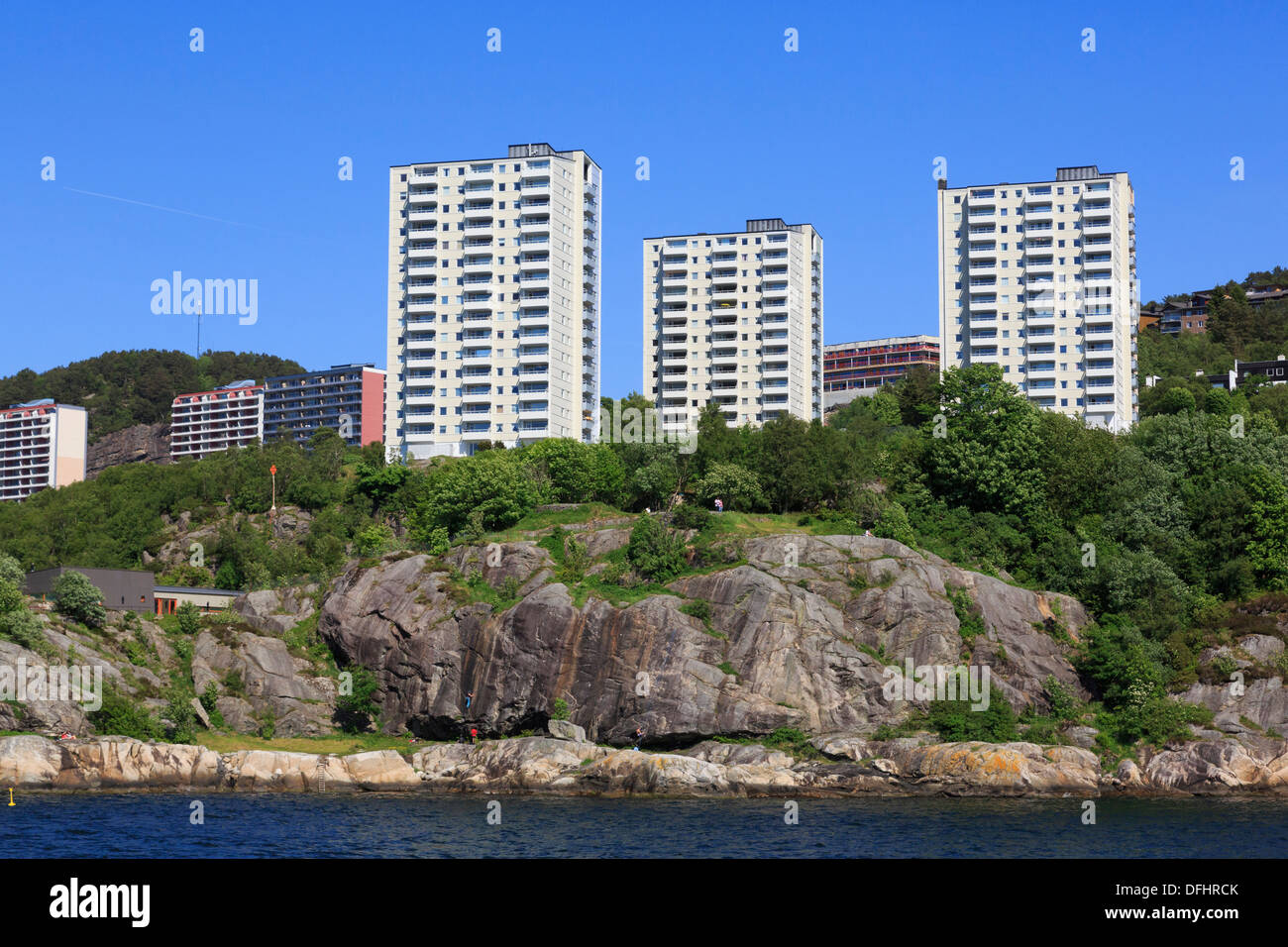 New hi-rise waterfront apartments above people climbing on rocks along Byfjorden fjord on the outskirts of Bergen, Norway - Stock Image