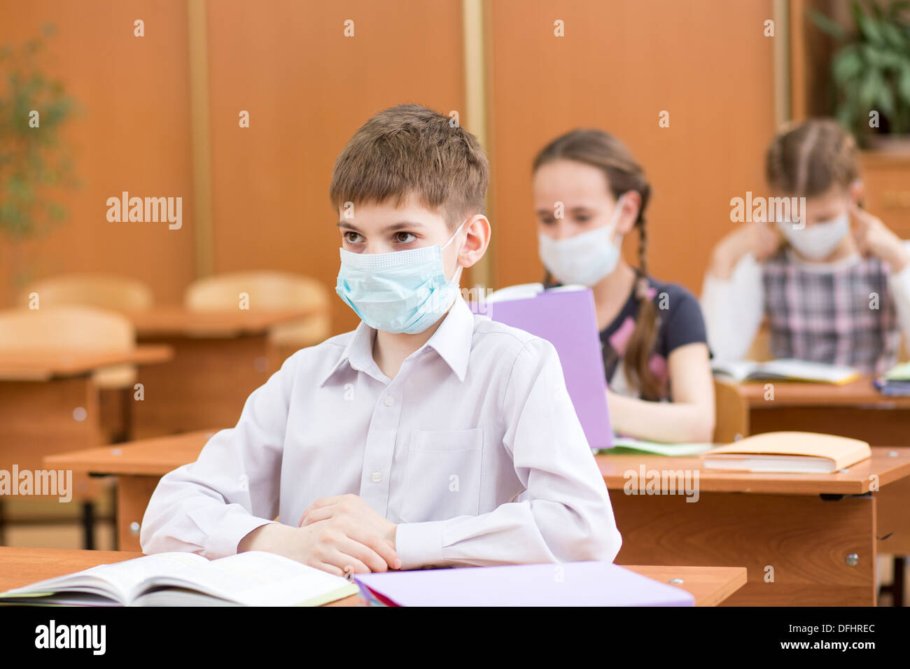 pupils with protection mask against flu virus at lesson - Stock Image