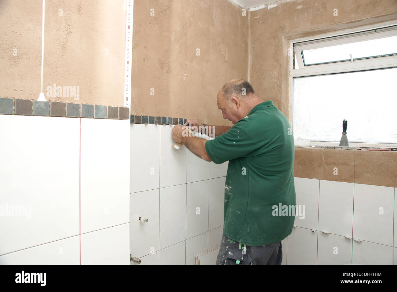 Tiler attaching tiles in a wet room / shower / bathroom on a newly ...