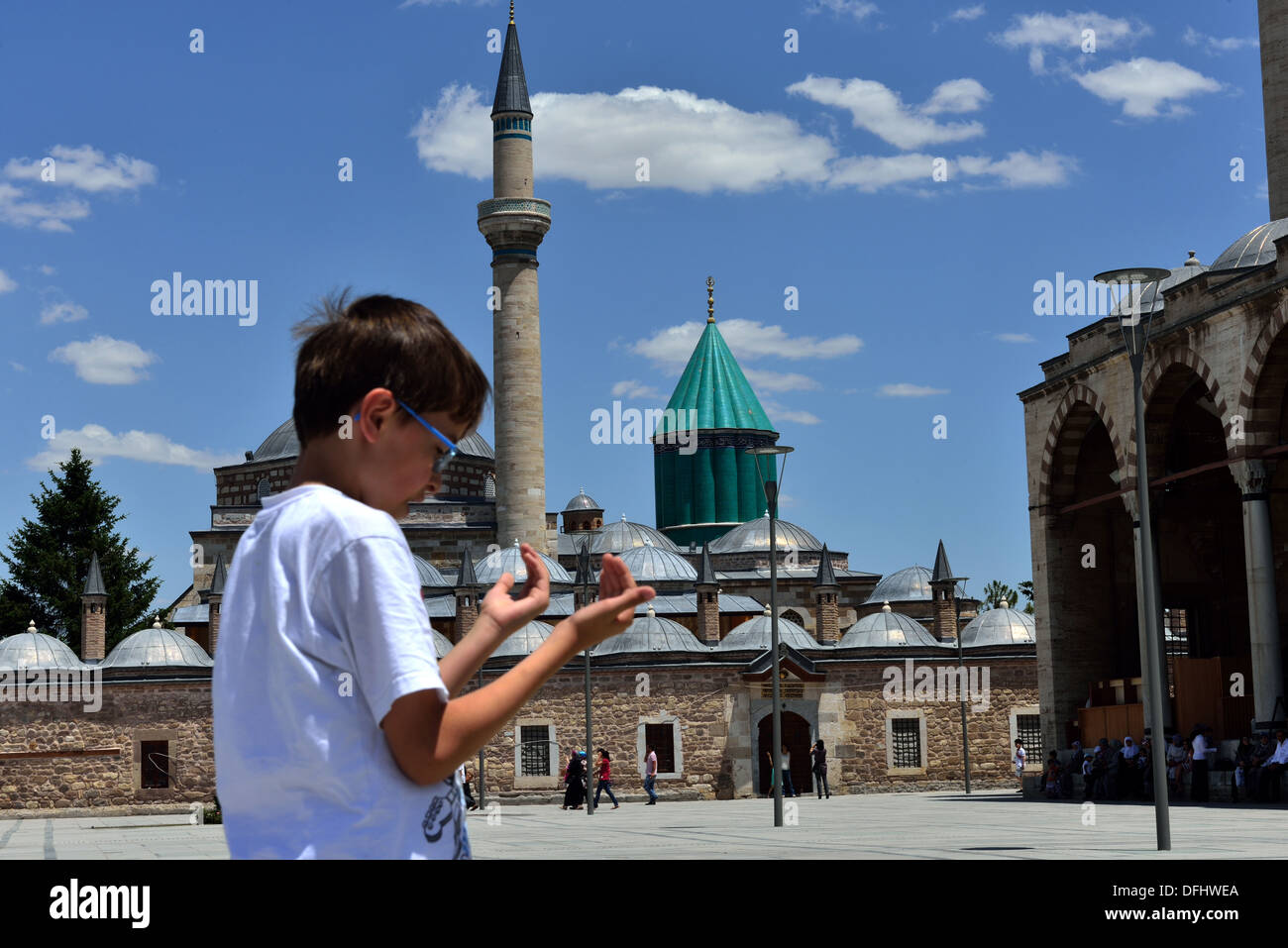 child praying in front of the tomb of Mevlana - Stock Image