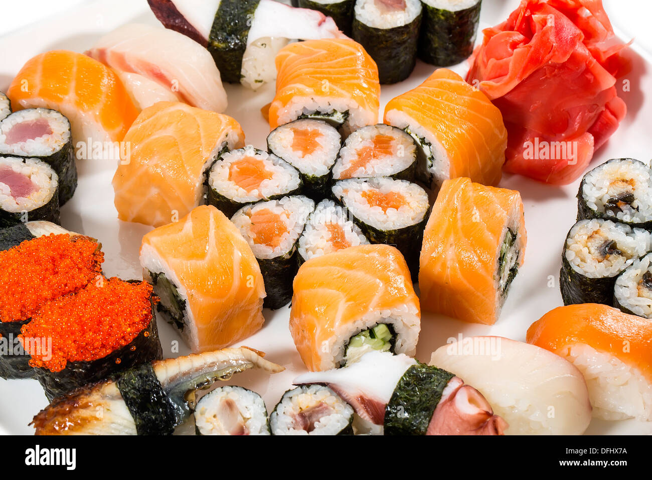 Japanese rolls in a restaurant with fish and vegetables - Stock Image