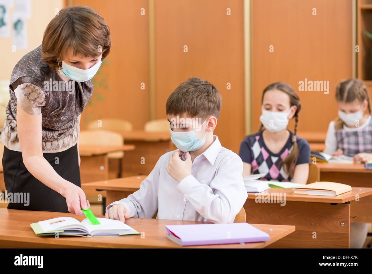 school kids and teacher with protection mask against flu virus at lesson - Stock Image