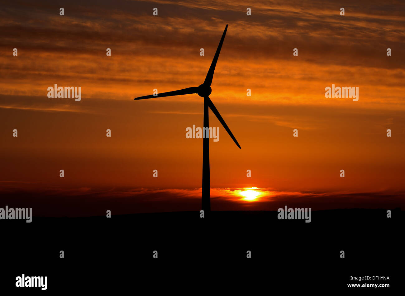 Wind turbine with nuclear powered sun at sunset near Gooseham in Cornwall England - Stock Image