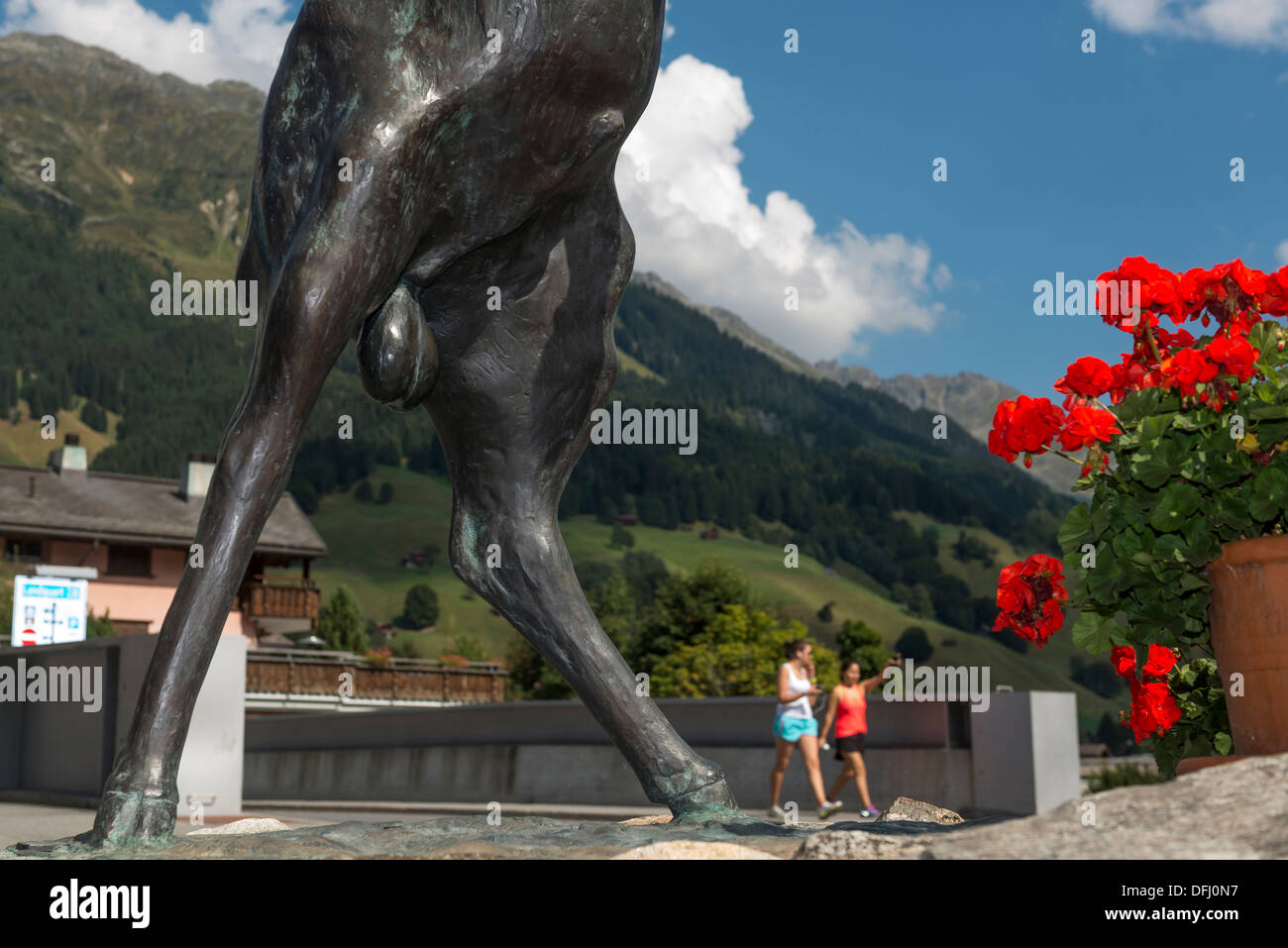 Two women walking past the genitalia area  of a male mountain goat or Alpine ibex statue. Klosters. Graubunden. Switzerland - Stock Image
