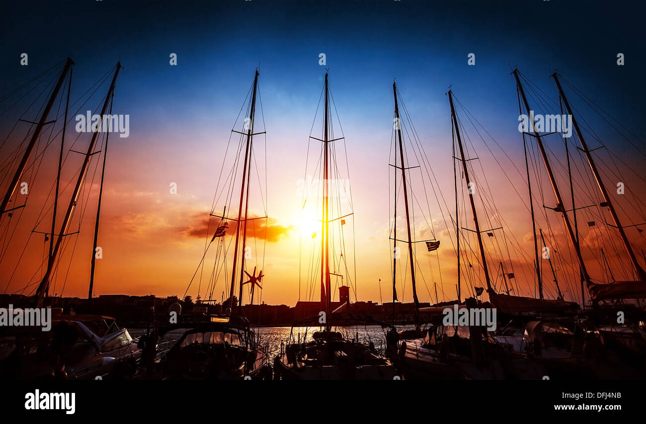 Sailboats mast on beautiful sunset background, harbour for sail yacht in the night, old marina in European city - Stock Image