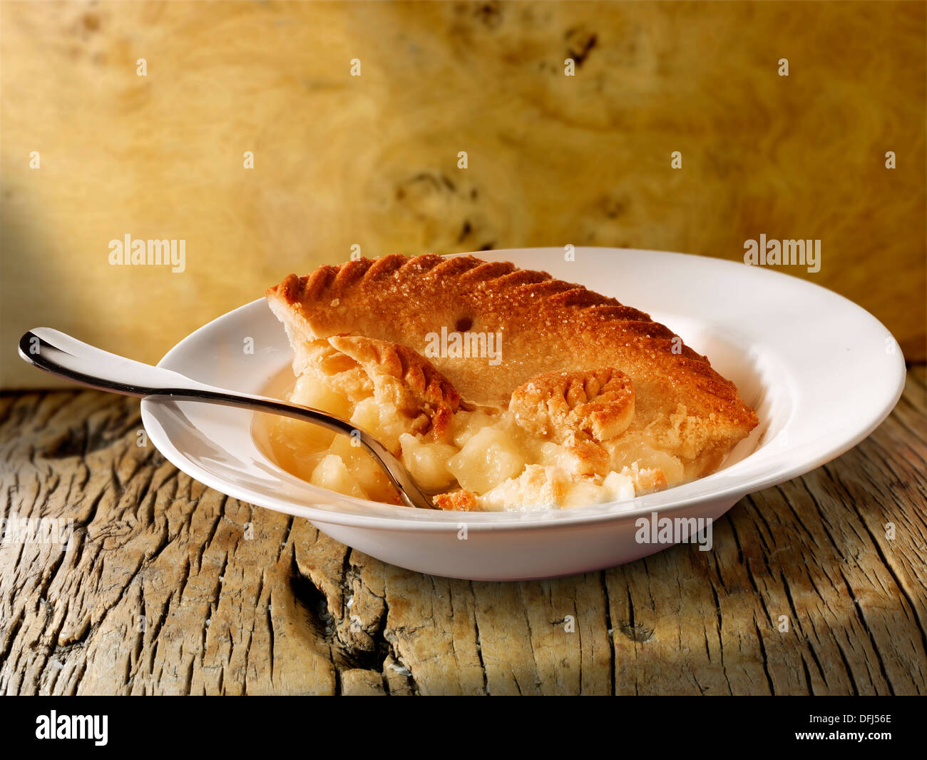 Traditional British apple pie and custard pudding served in a bowl on a wood table - Stock Image