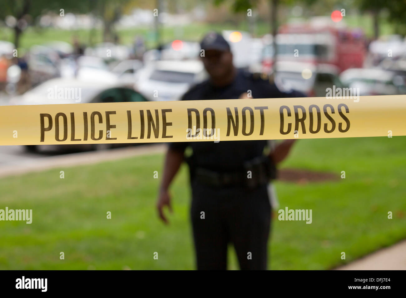 Policeman standing behind police line tape at a crime scene - Washington, DC USA - Stock Image