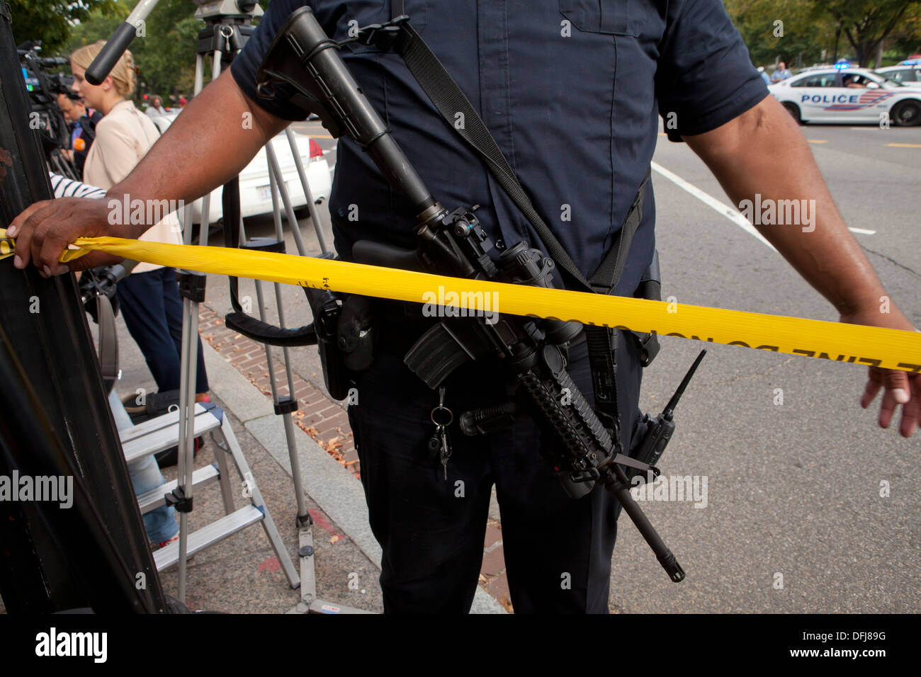Policeman carrying a semi-auto rifle putting up police line tape at a crime scene - Washington, DC USA - Stock Image