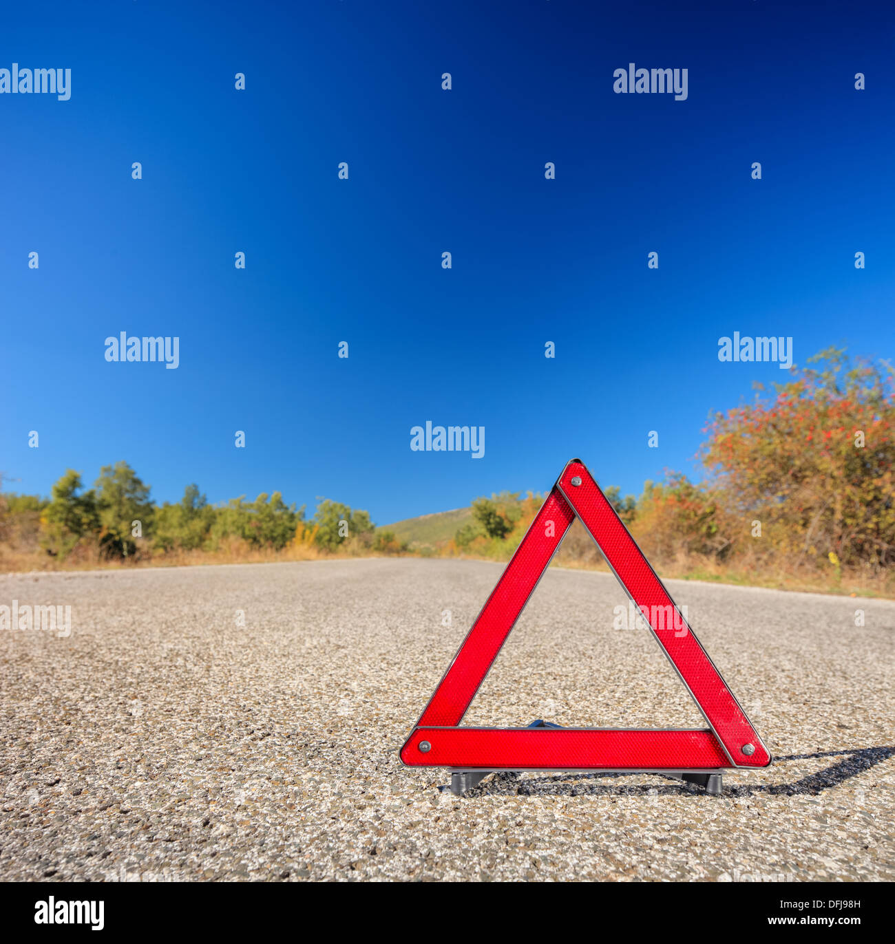 View of a red warning triangle on a road - Stock Image