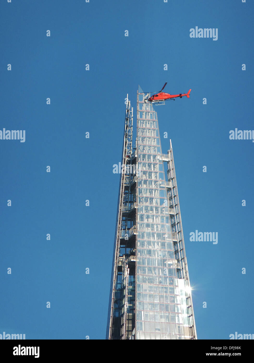 optic illusion suggesting a helicopter crashing into a glass building in London - Stock Image