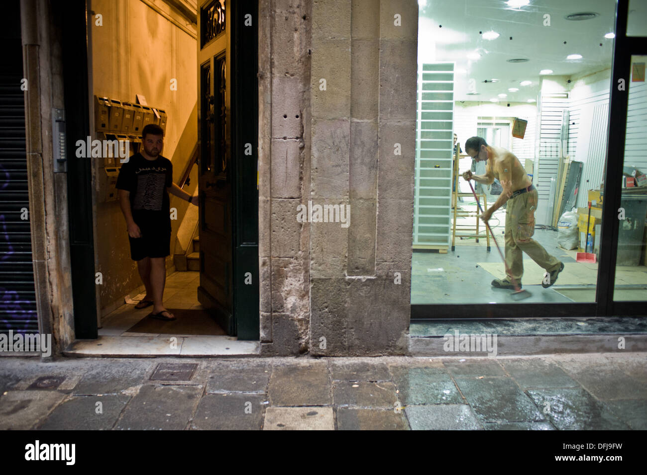 Everyday  scene in Banys Nous Street in the Gothic Quarter of  Barcelona during a wet and rainy day. - Stock Image