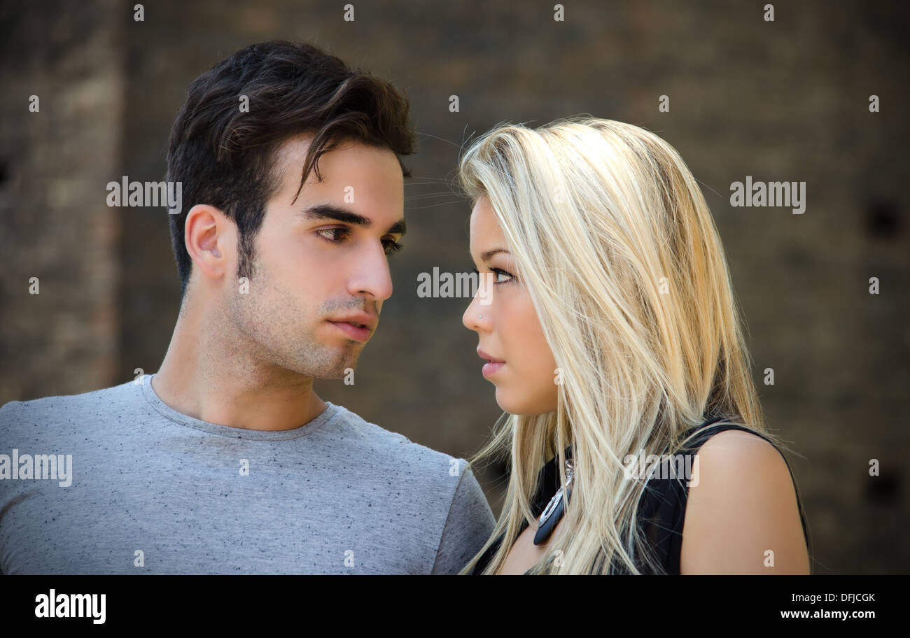 Attractive couple in love looking into each other's eyes, blonde girl, brown haired guy, outdoors - Stock Image