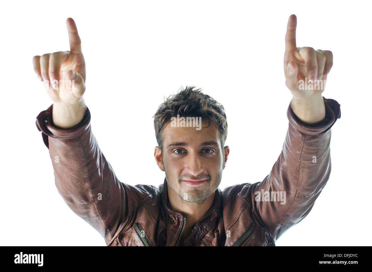 Smiling and confident young man pointing fingers up and looking in camera, isolated on white - Stock Image