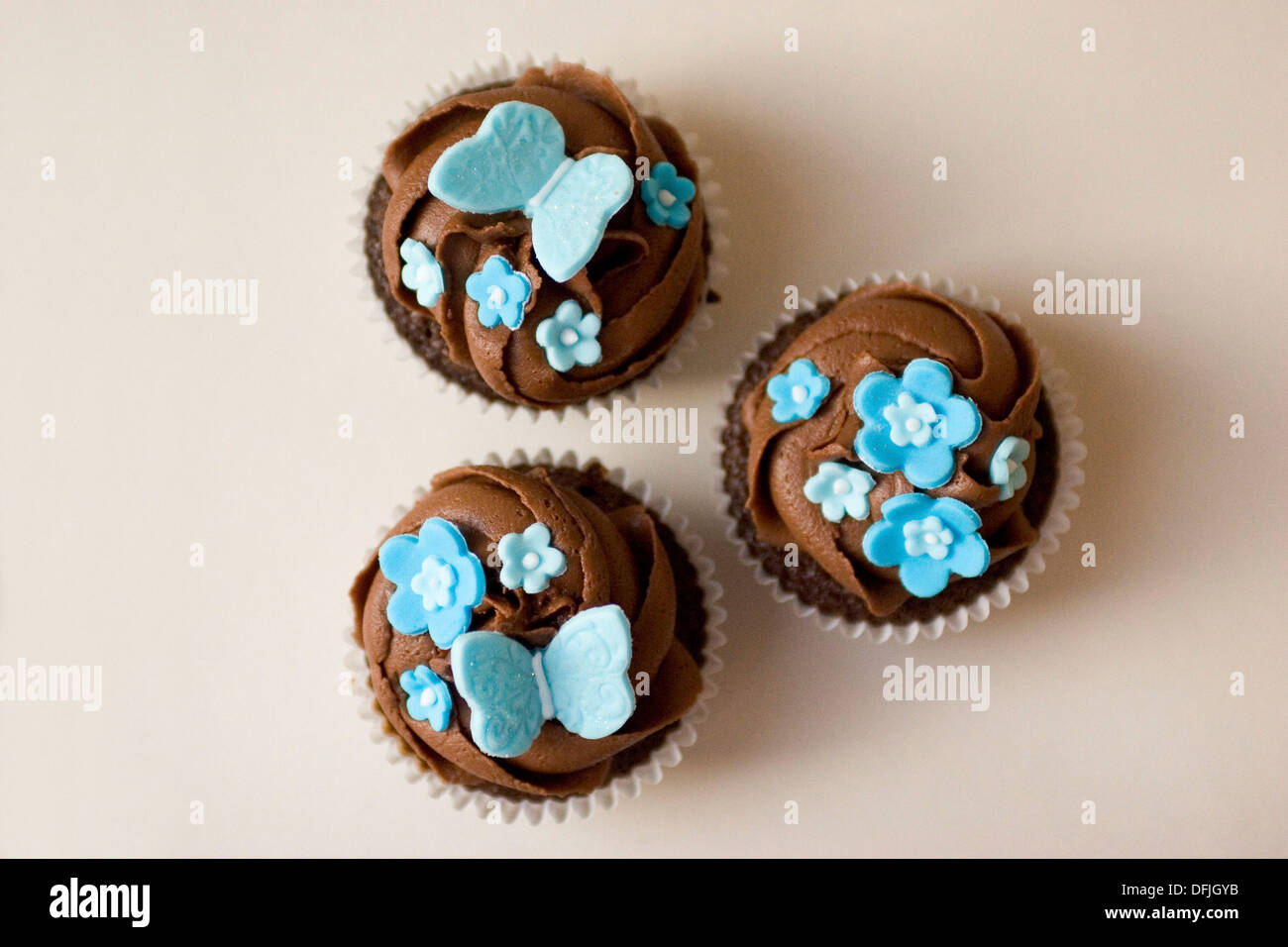 Three Cupcakes With Chocolate Frosting Swirl And Blue Butterfly And