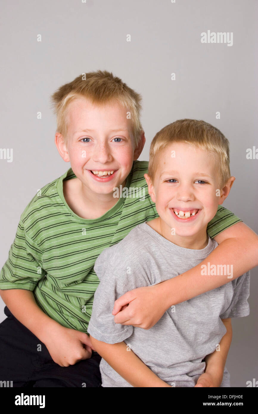 A pair of young blond haired boys, brothers, against a grey background - Stock Image