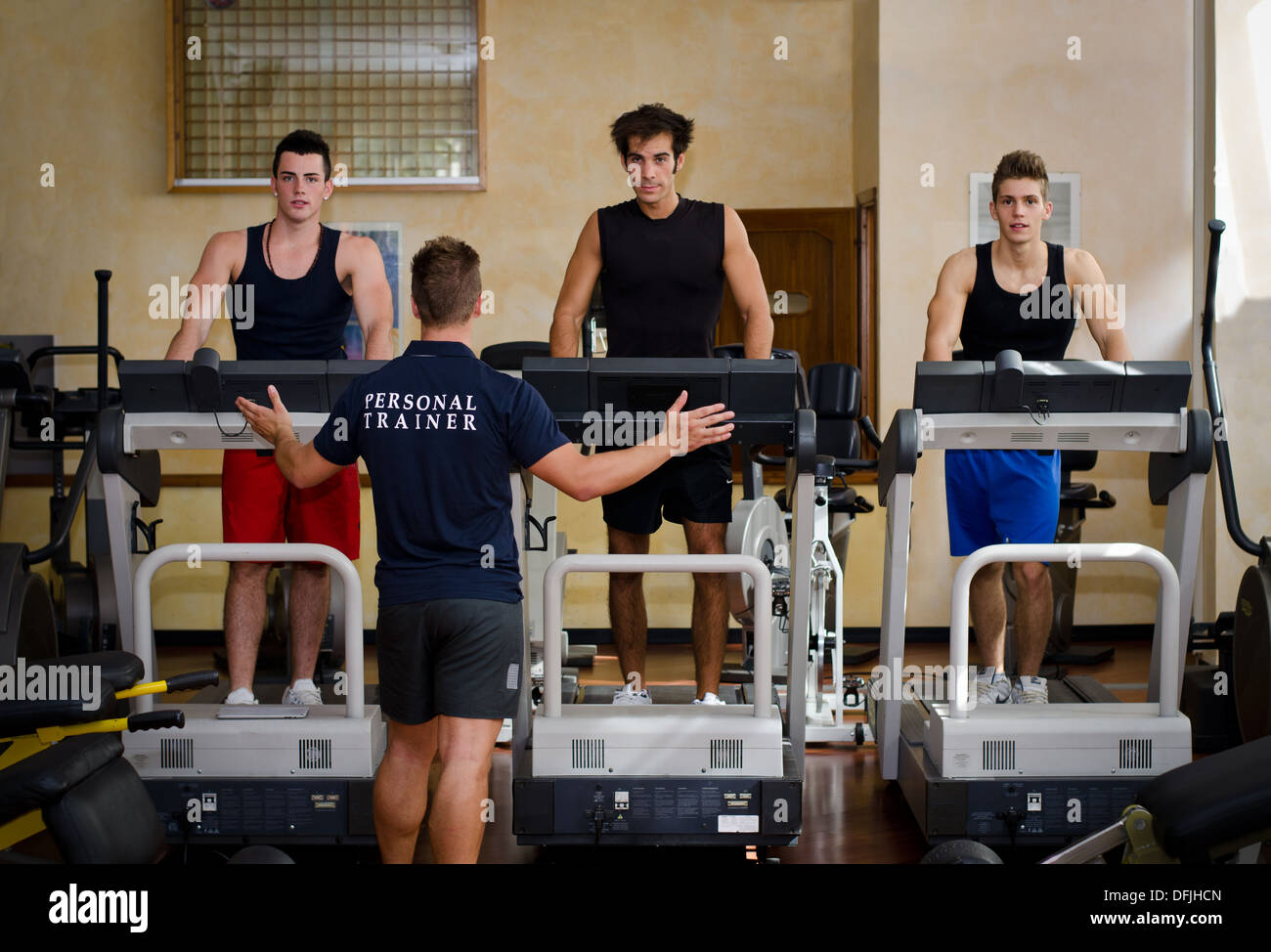 Three young men exercising on treadmills with personal trainer in a gym. - Stock Image