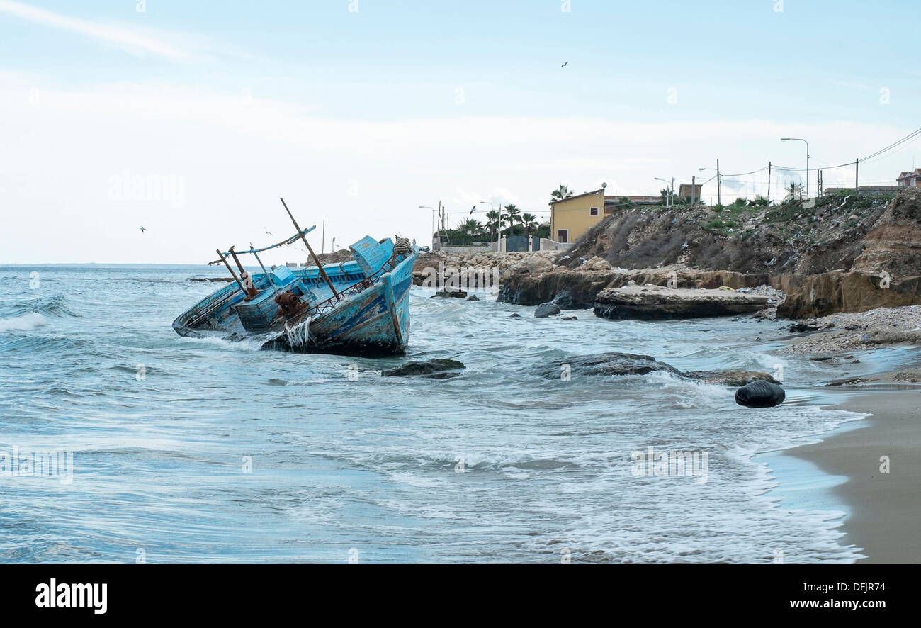 A beached African migrants boat at Marina di Avola, Sicily, Italy, Mediterranean sea - Stock Image