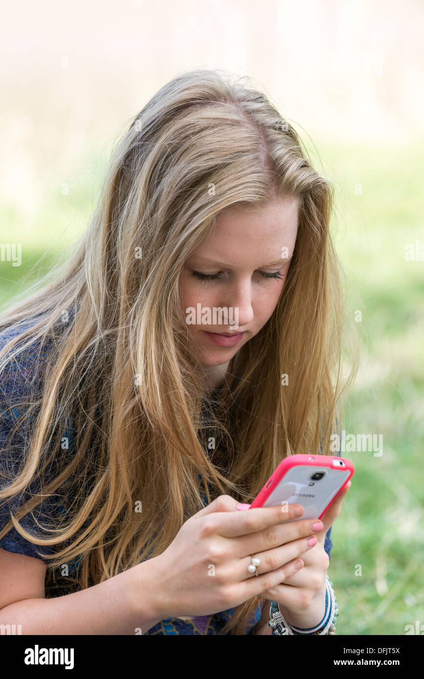 YOUNG GIRL, TEENAGER AGED SEVENTEEN,TEXTING ON CELL /MOBILE PHONE OUTDOORS - Stock Image