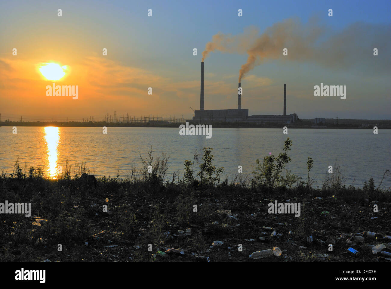 Power plant in beams of the coming sun. In the foreground it is a lot of garbage. - Stock Image