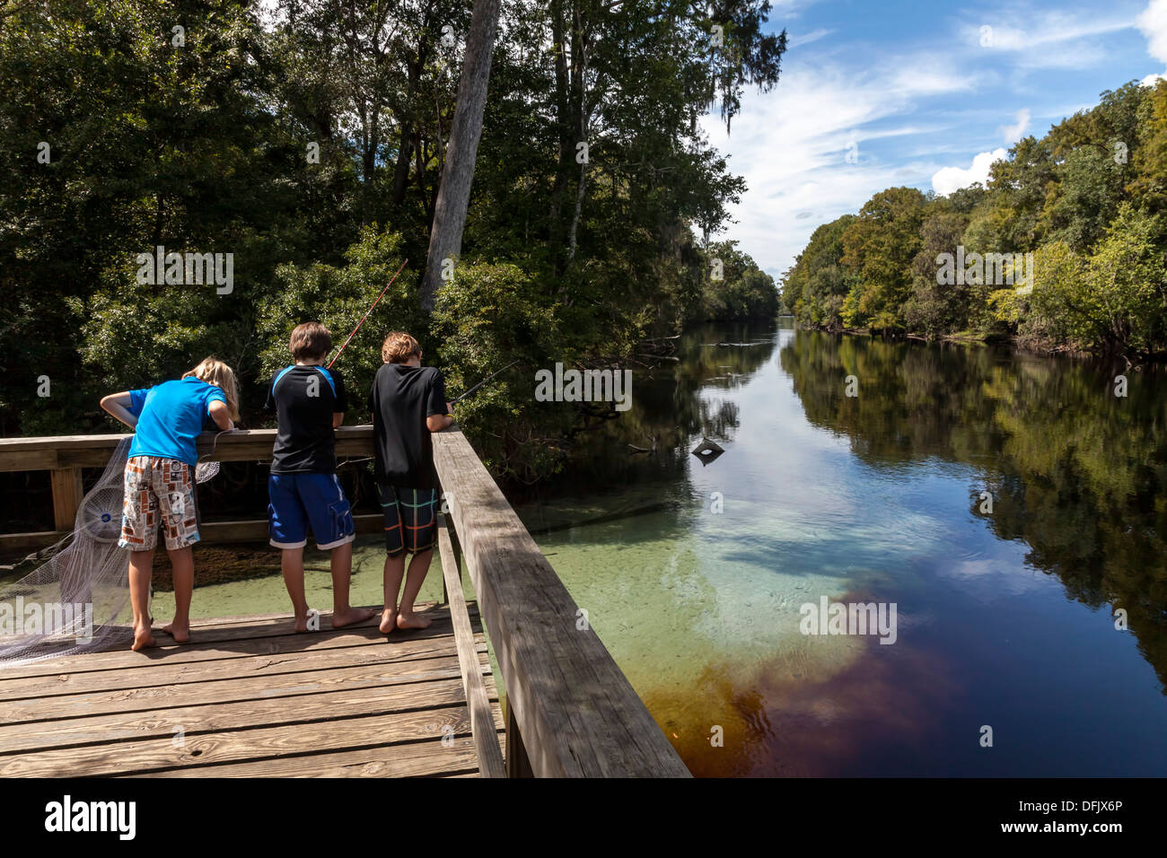 Three young boys fishing from dock where crystal clear spring water enters the Santa Fe river blackened by root tannins. - Stock Image