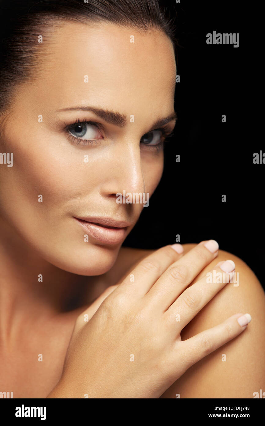 Closeup image of face of beautiful young woman with perfect skin. Beautiful young woman with glowing complexion - Stock Image