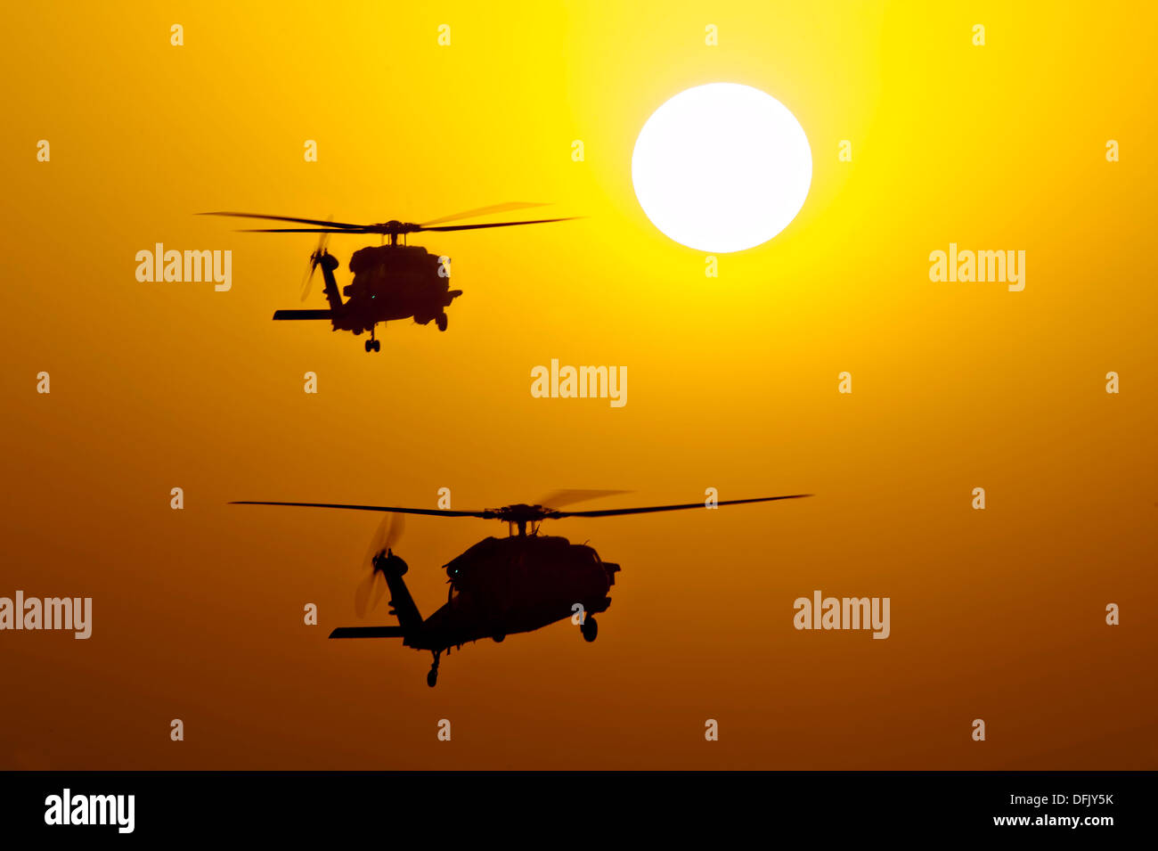 US Navy MH-60S Knighthawk helicopters are silhouetted by the setting sun as they patrol near the aircraft carrier - Stock Image