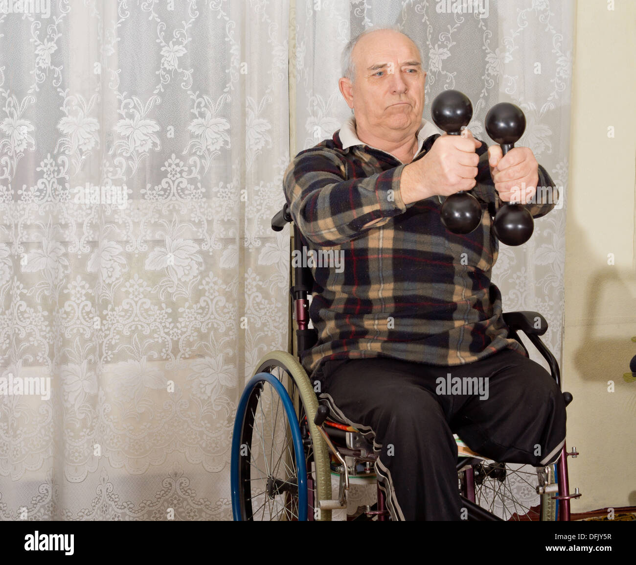 Senior handicapped man exercising with a pair of dumbbells to strengthen his arms while sitting in a wheelchair - Stock Image