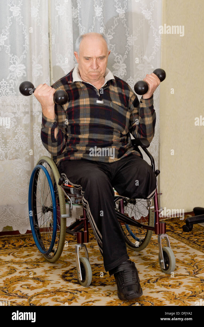 Senior disabled man exercising with dumbbells - Stock Image
