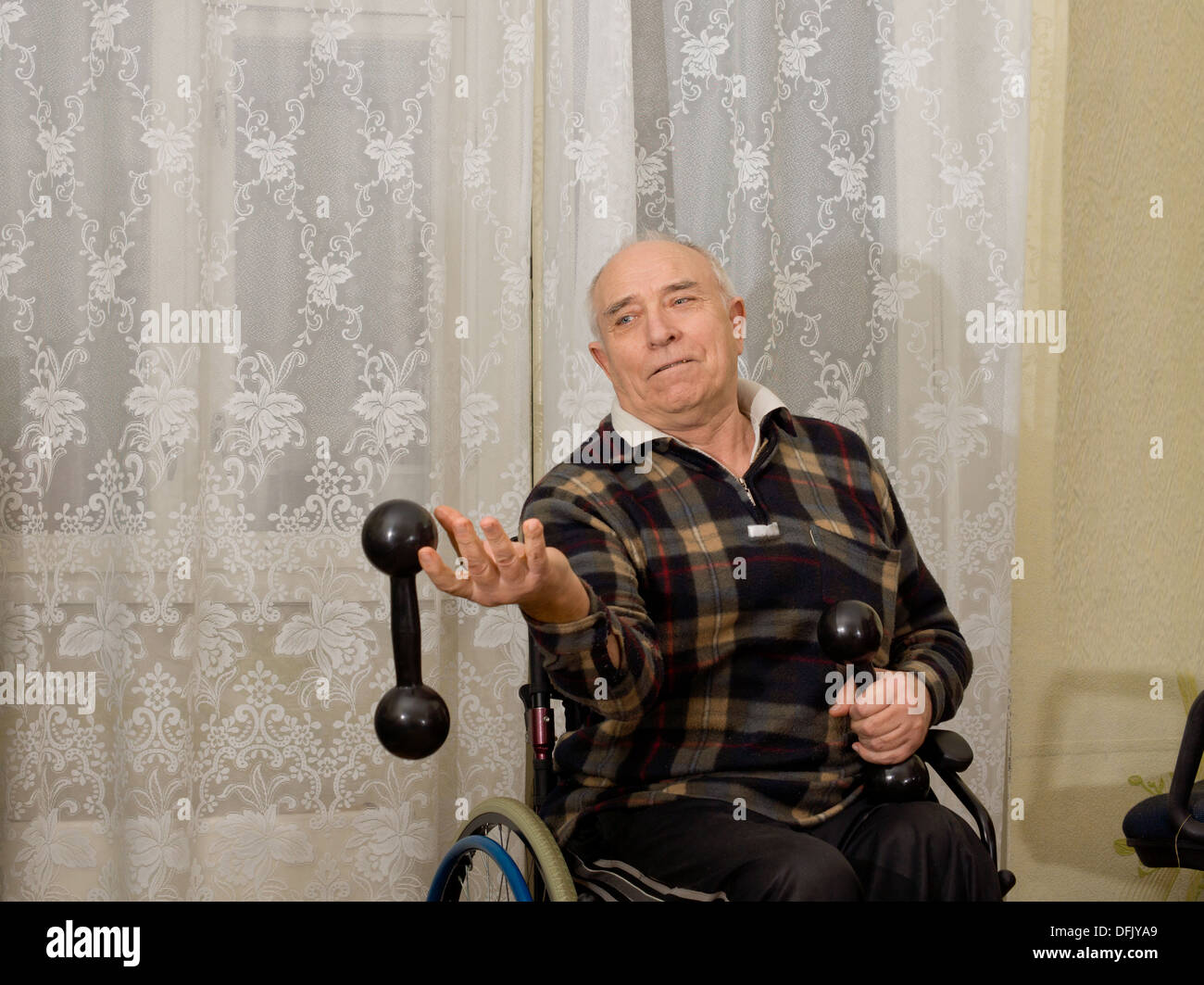 Elderly man in a wheelchair exercising with a pair of dumbbells looking frustrated as he drops one by mistake, with copyspace - Stock Image