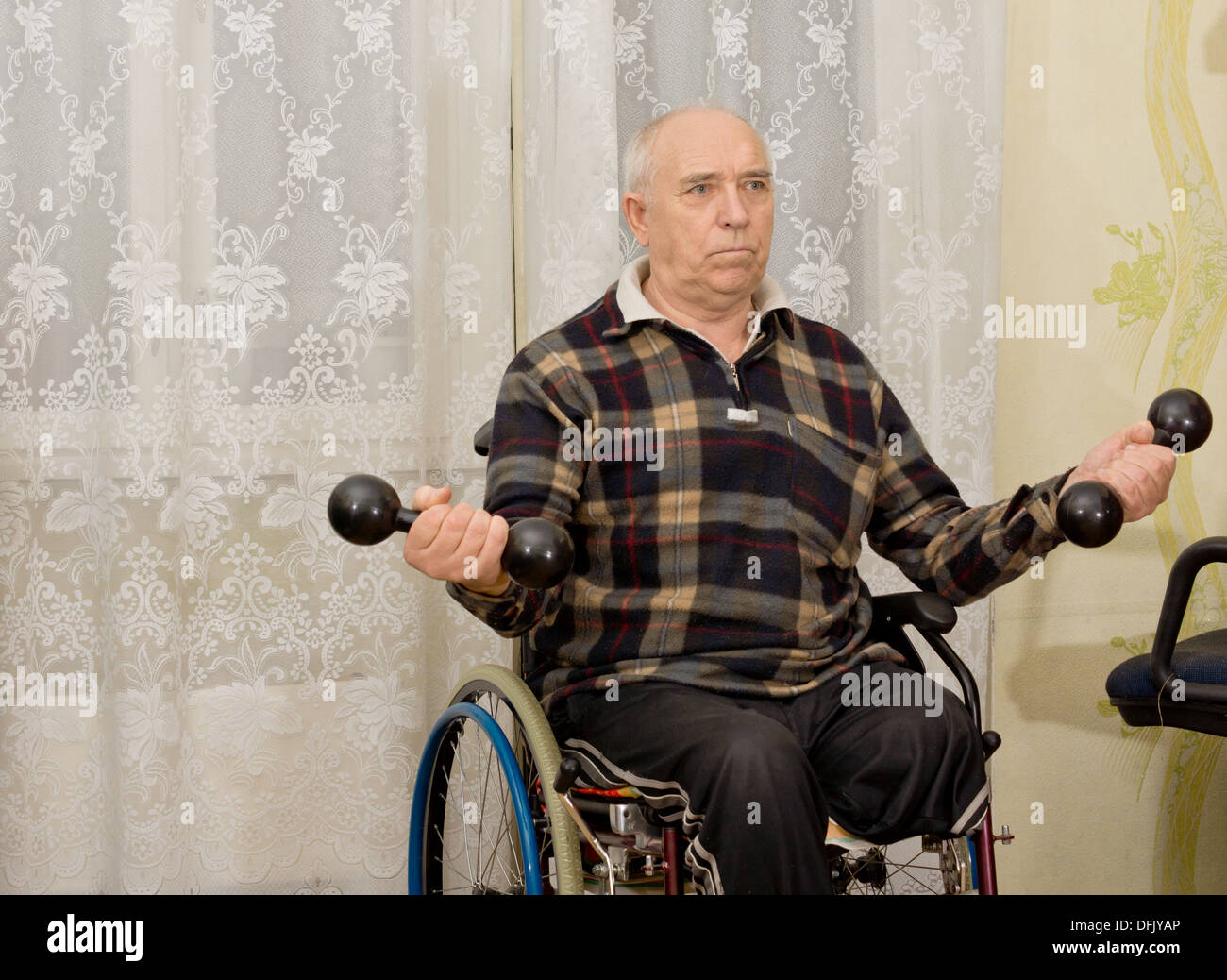 Senior handicapped male amputee sitting in his wheelchair doing exercises working out with a pair of dumbbells - Stock Image