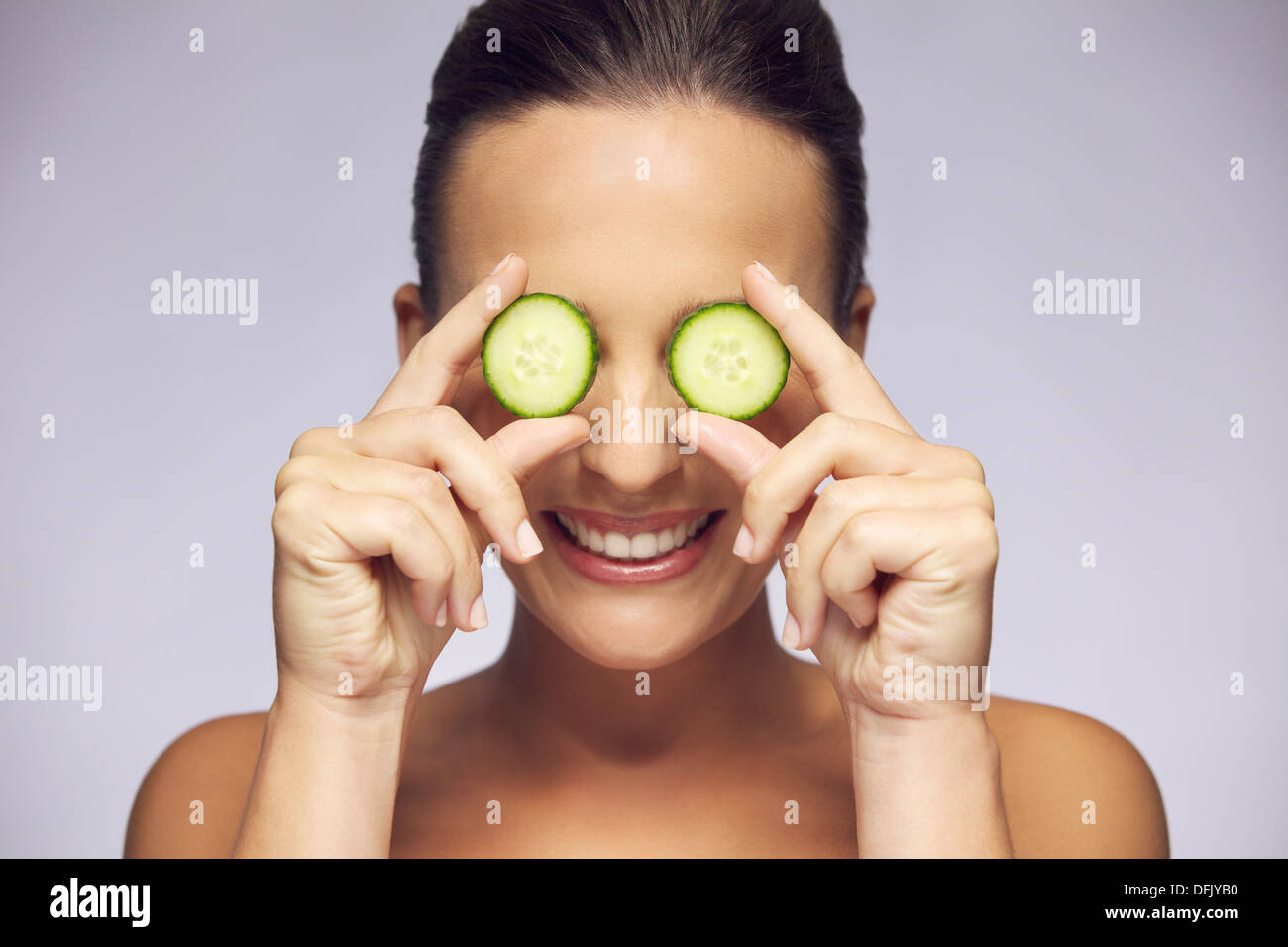 Beautiful and smiling young woman holding slice of cucumber in front of eyes on gray background. Eye care concept - Stock Image