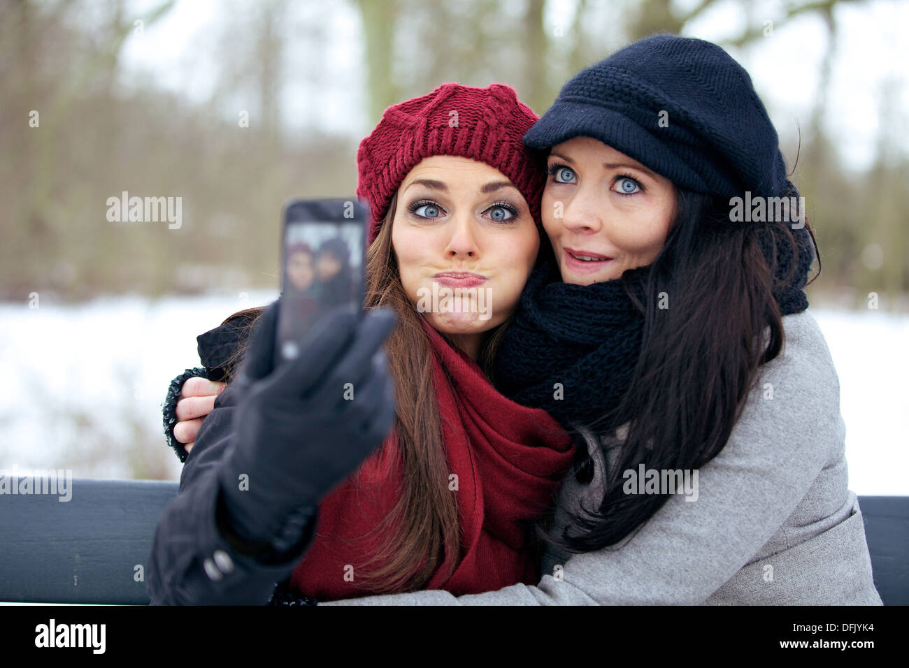 Friends with camera phone having fun by making faces - Stock Image
