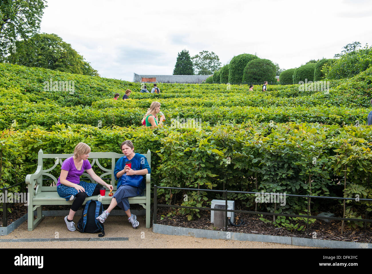 LONDON, UK - AUGUST 13: Side view of people walking up shrubbery maze leading to the grounds of Kensington Palace, Stock Photo