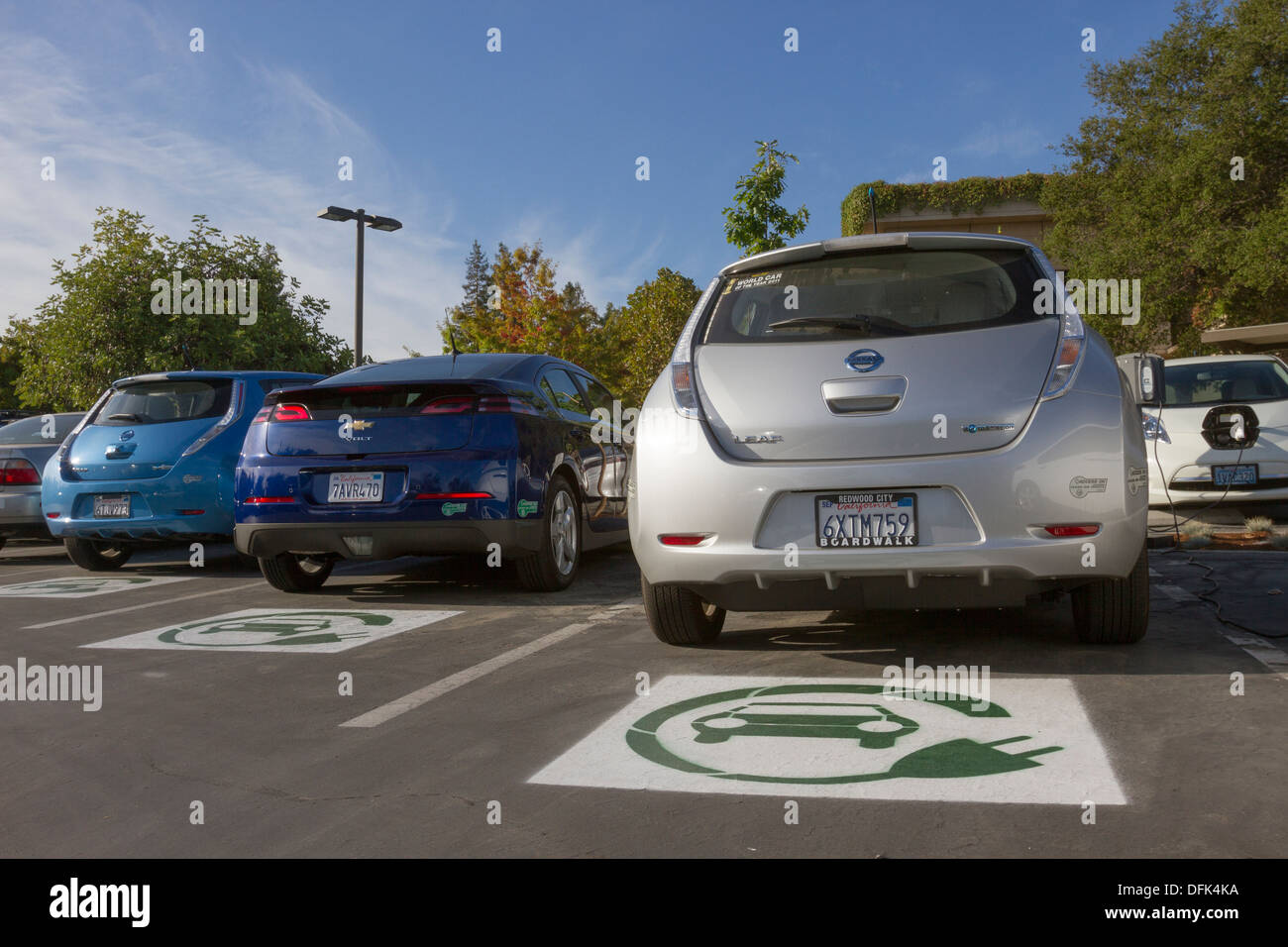 EV symbol painted on parking spaces for to plug-in electric cars in a company parking lot - Stock Image