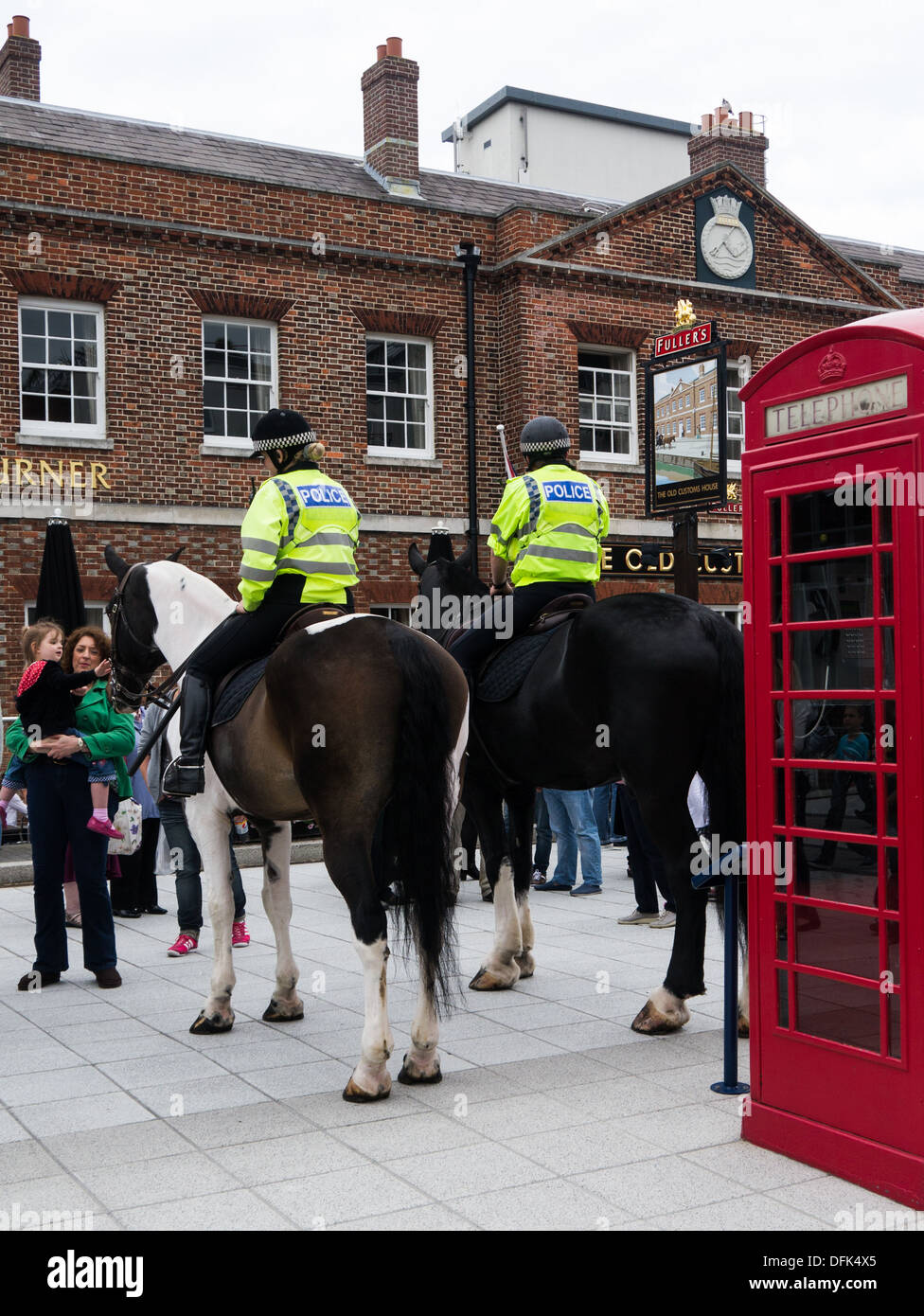 Two mounted police officers on horseback in front of a typical English pub and a red telephone box - Stock Image