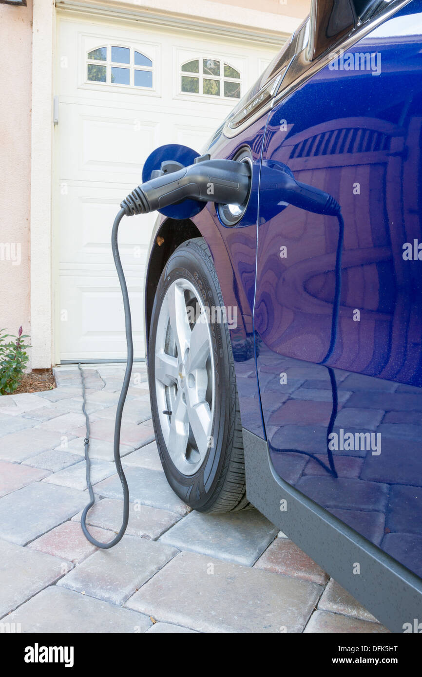 Plug-in hybrid electric car with connector plugged and charging parked at home in a driveway Stock Photo