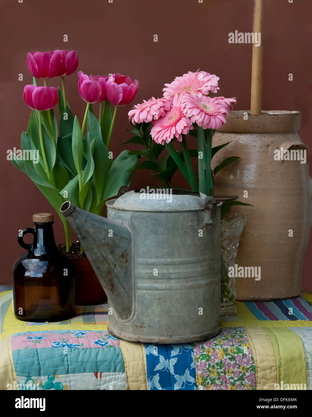 An old watering tin, jug, flowers and a butter churn. - Stock Image