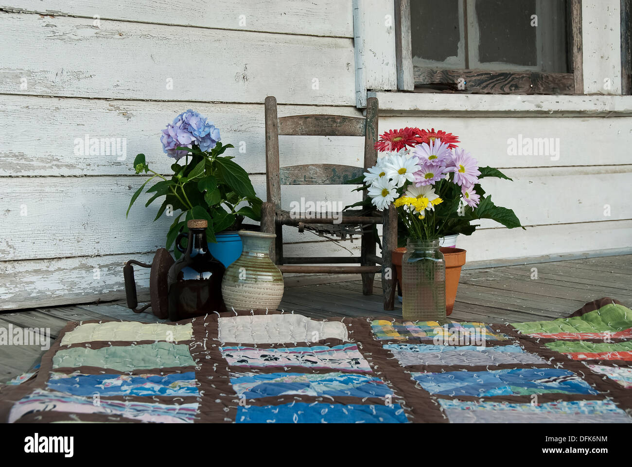 An old chair, vase, jug, flowers and a quilt on a rustic porch. - Stock Image