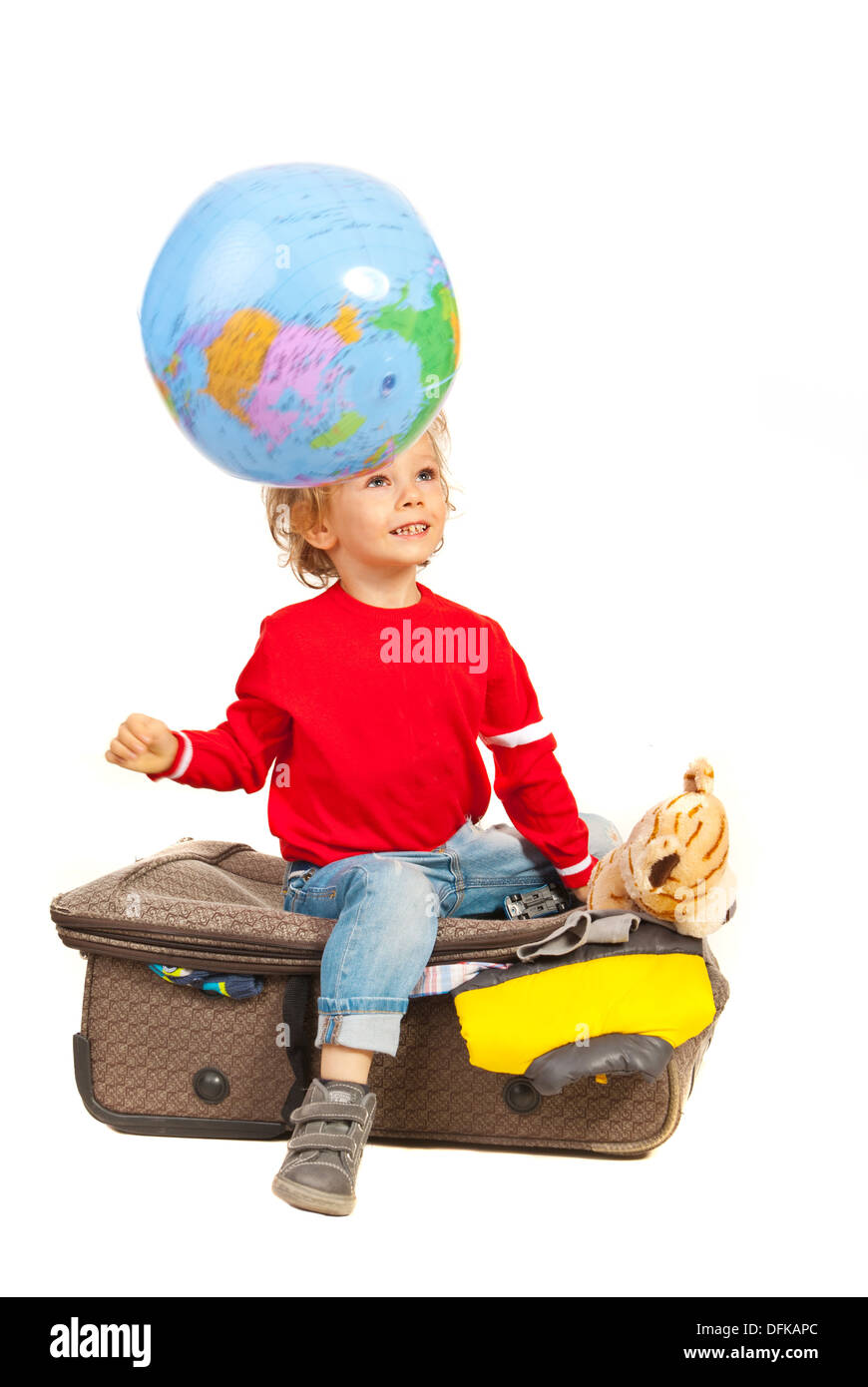 Child dreaming with open eyes and looking at world globe in motion and sitting on luggage against white background - Stock Image