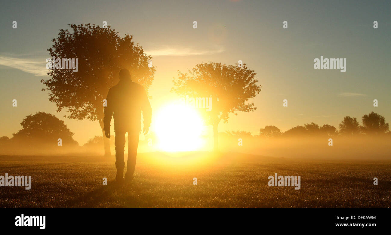 Peterborough, Cambridgeshire, UK. 6th October 2013.  A person out for a walk through the early morning mist at Nene Stock Photo