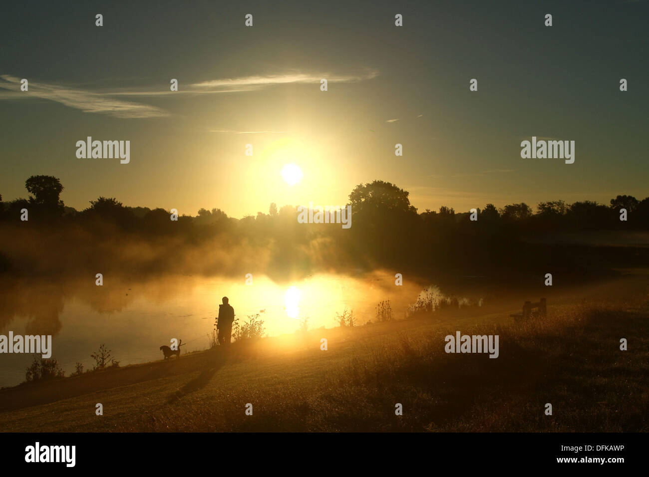 Peterborough, Cambridgeshire, UK. 6th October 2013.  A person out for an early morning walk through the mist at Stock Photo