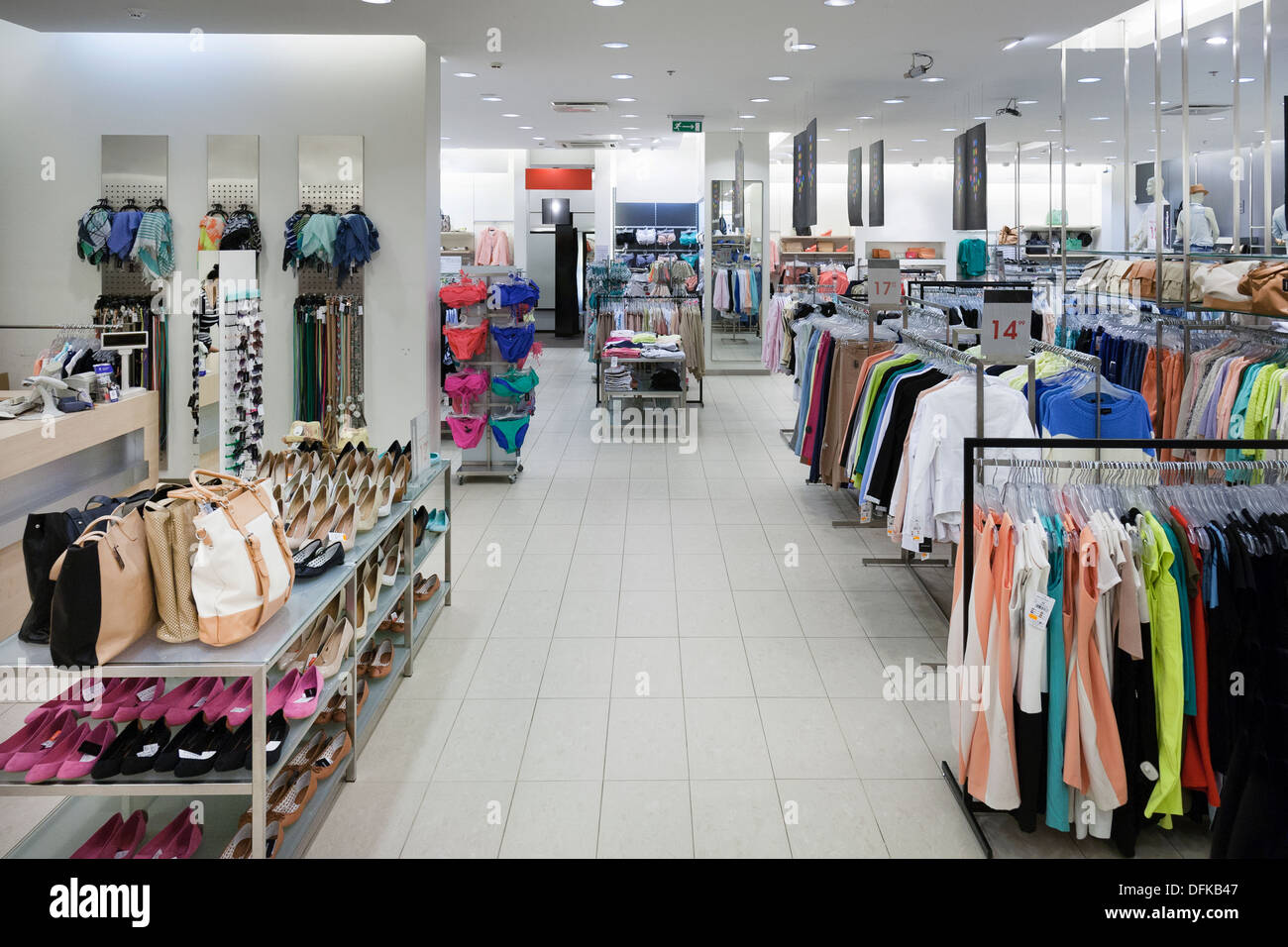 f62be98a9b Fashion shop interior with display. Clothing and bags in retail store.  Large aisle and elevated view