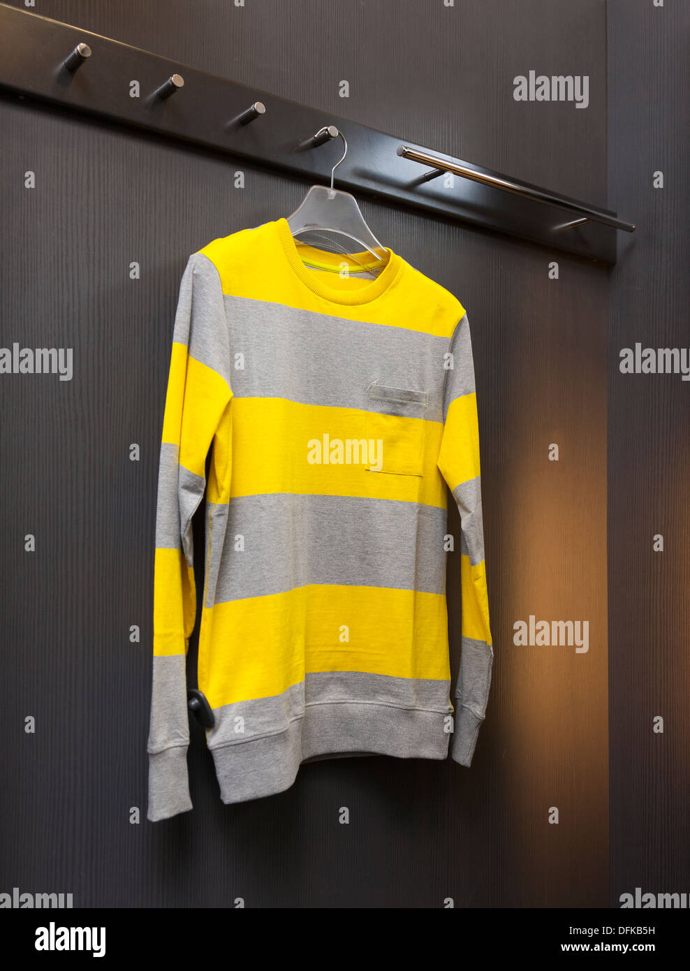 Close up of sweater, sweatshirt in retail shop dressing cabin. Changing room. - Stock Image