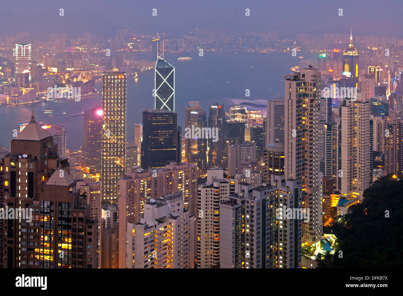 Night view over the skyscrapers in Central District and across the Victoria Harbour to Kowloon, Hong Kong - Stock Image