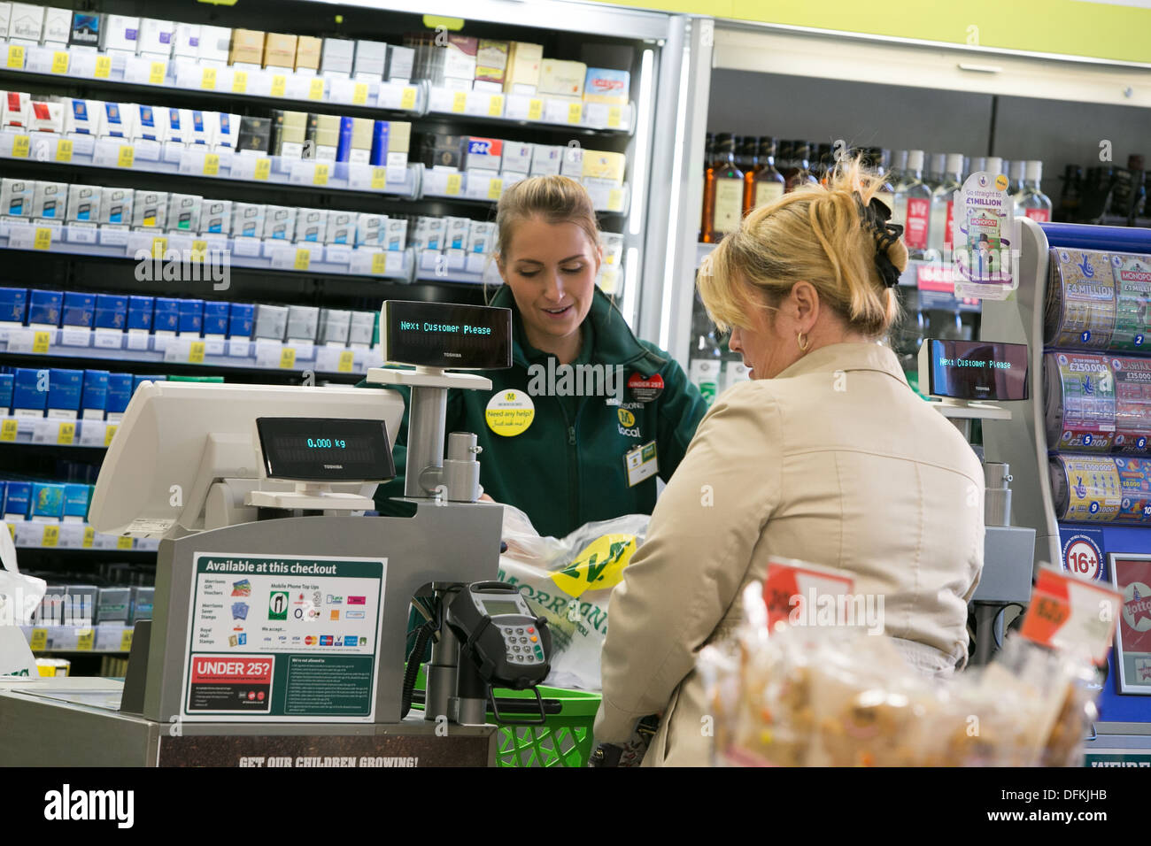 Morrisons M Local at Vicar Lane Shopping Centre , Chesterfield . A member of staff serves a customer - Stock Image