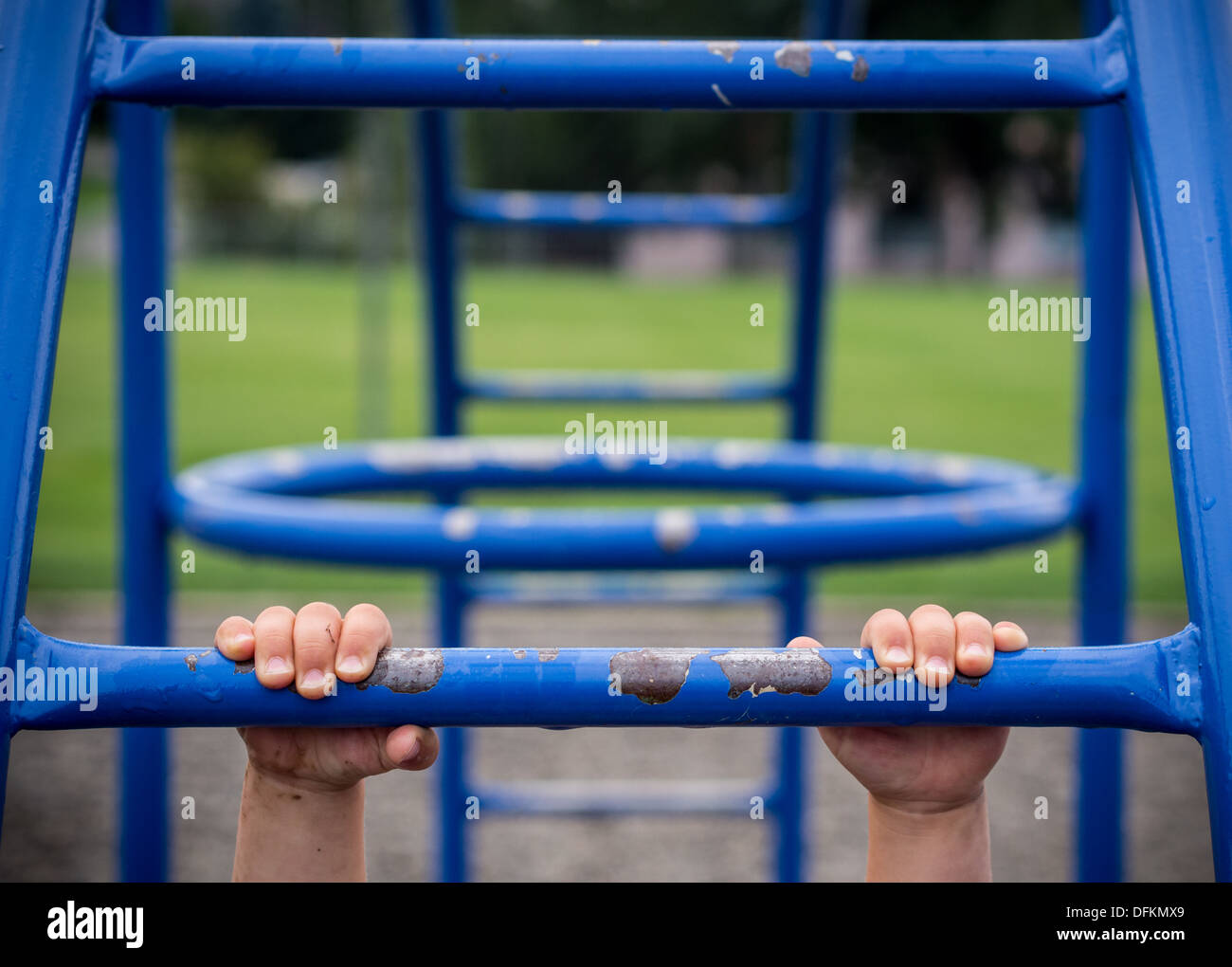 Hold on concept with child hanging on monkey bars - Stock Image