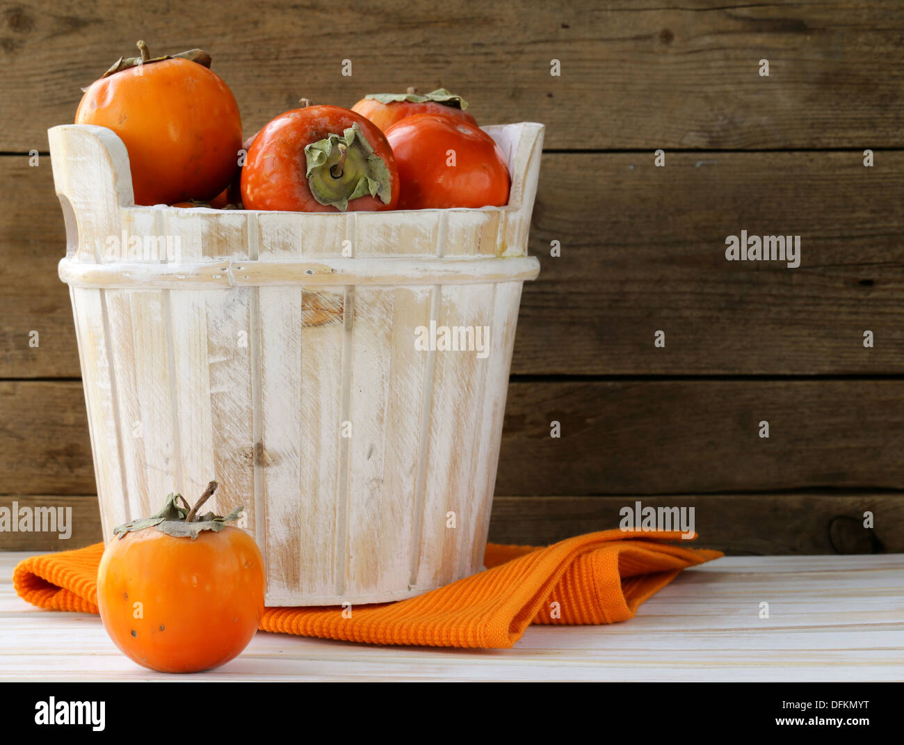 Orange ripe persimmon in a wooden table - Stock Image