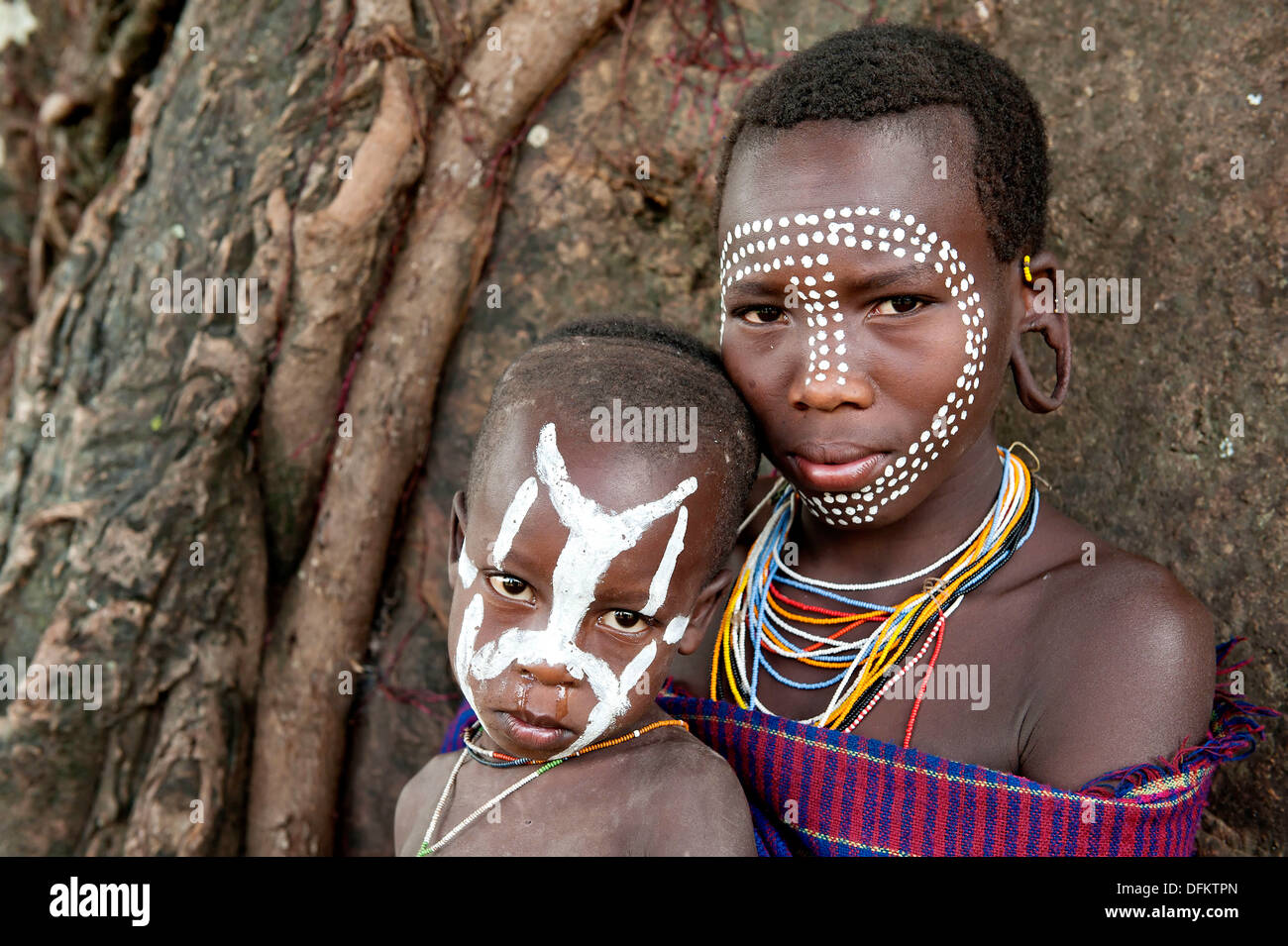 Painted faces of a young Surma Women and her child in front of a tree, Kibish, Omo River Valley, Ethiopia - Stock Image