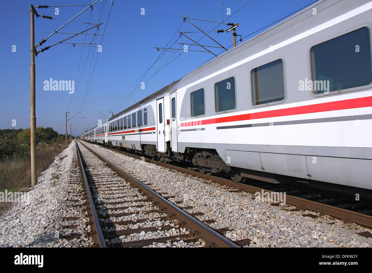 Passenger train passing railroad on a sunny day - Stock Image