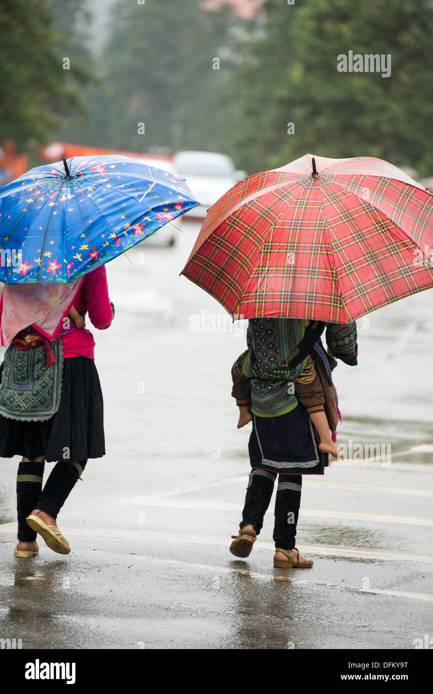 Minority group Black Hmong ladies walk in the downtown in the raining, Sa Pa, Vietnam - Stock Image